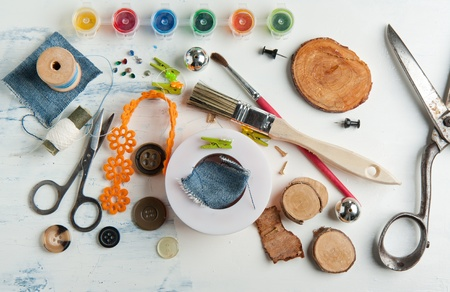Still life of spool of thread, buttons, scissors and brushes on white table photo