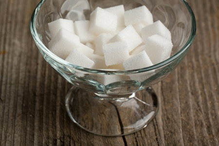 Glass vase of white sugar on old wooden table photo