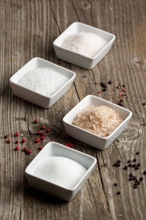 Various of four kind of salt in white plates and pepper on old wooden table Stock Photo - 11107355