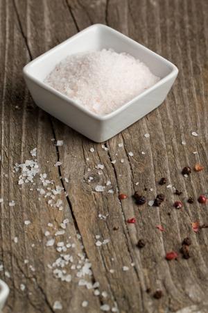 Plaat van roos zout op oude houten tafel Stockfoto