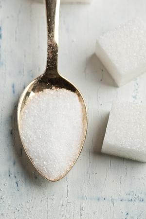 Bovenaanzicht op theelepeltje met witte suiker op witte houten tafel