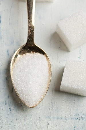 Top view on teaspoon with white sugar on white wooden table