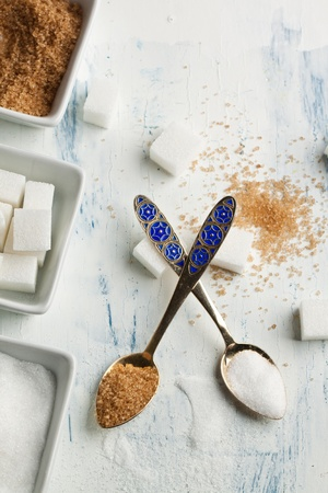 Top view on teaspoons and plates with various of white and brown sugar on white wooden table photo