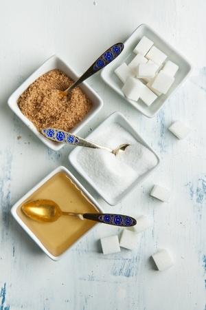 Varios de azúcar blanco y marrón con la miel en las placas blancas en la mesa de madera blanca