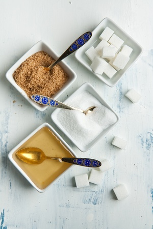 Various of white and brown sugar with honey in white plates on white wooden table