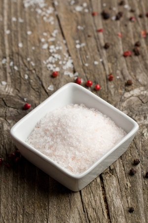 White plate of rose sea salt and pepper on old wooden table