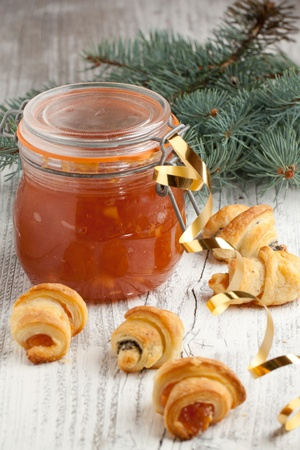 Glass jar of homemade apple jam and cookies near christmas tree photo