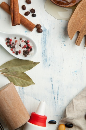 Kitchen background with kitchen utensil, coffee beans, salt and pepper on white wooden table photo
