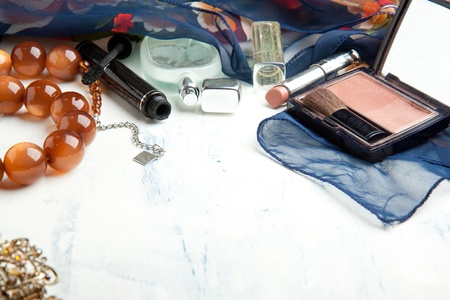Various cosmetics and beads on white wooden table photo