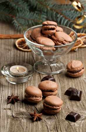 Chocolate macaroons with pieces of black chocolate and anise on old wooden table with christmas tree