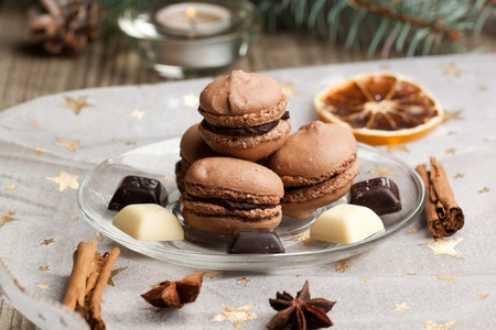 Plate of chocolate macaroons with pieces of white and black chocolate and species on christmas cloth with golden stars photo