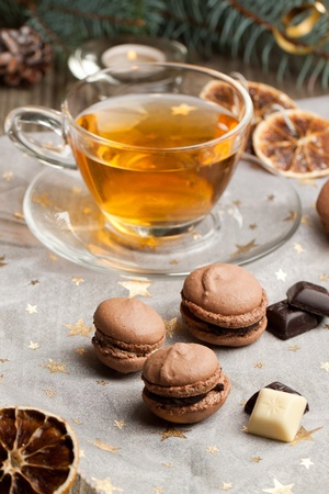 Chocolate macaroons with pieces of white and black chocolate and cup of hot tea on white christmas cloth photo