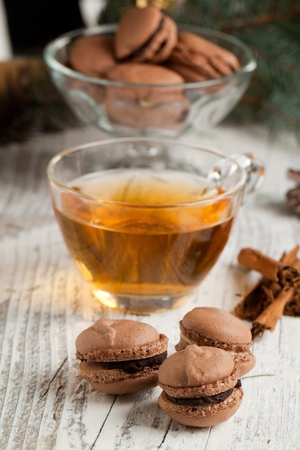 Chocolate macaroons with cup of hot tea on old wooden table photo
