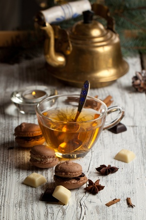 Chocolate macarons with pieces of white and black chocolate and cup of hot tea on old wooden table photo