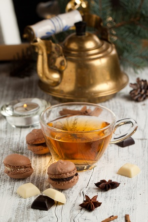 Chocolate macaroons with pieces of white and black chocolate and cup of hot tea on old wooden table photo