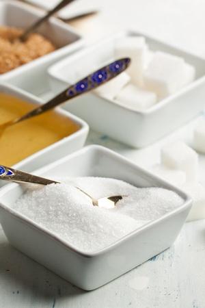 Verschiedene von weißen und braunen Zucker in weißen Platten auf Holztisch Lizenzfreie Bilder