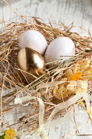 White and golden easter eggs in nest photo