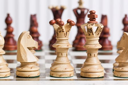 Black and white chess figures on chess desk photo
