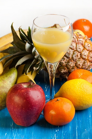 Nature morte avec des fruits frais divers et le verre de jus sur la table en bois bleu