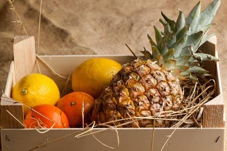 Wooden box of fresh various fruits on sacking cloth photo