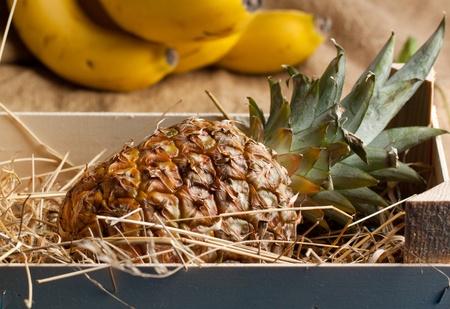 Frutas tropicales de piña en caja de madera Foto de archivo