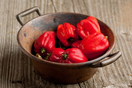 tex: Vintage bowl of red chili habanero peppers on old wooden table Stock Photo