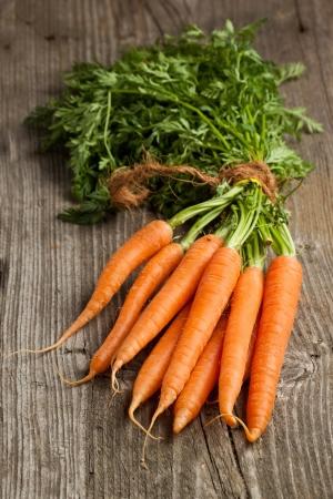 zanahoria: Recién lavadas las zanahorias enteras en la mesa de madera vieja Foto de archivo