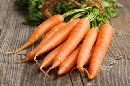 Recién lavadas las zanahorias enteras en la mesa de madera vieja Foto de archivo