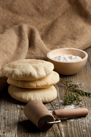 Three fresh pitas bread, thyme and bowl of flour on old wooden table Stock Photo