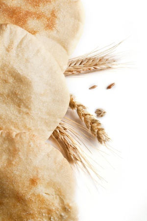 Fresh pitas bread with ears of rye and wheat over white background photo