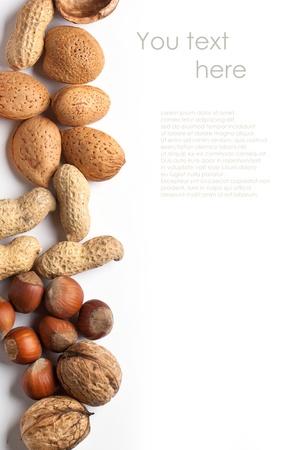 Achtergrond met diverse nootjes amandel, hazelnoot, walnoot en pinda's op een witte met voorbeeld tekst