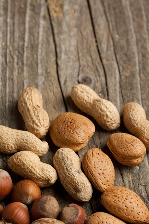 Background with assorted nuts almond, hazelnut and peanut on old wooden table photo