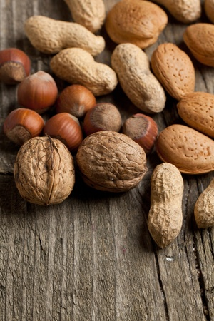 Background with assorted nuts almond, hazelnut, walnut and peanut on old wooden table photo