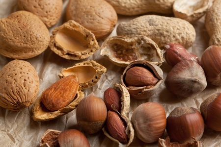 Assorted of whole and chopped nuts almond, hazelnut and peanut on crumpled paper photo