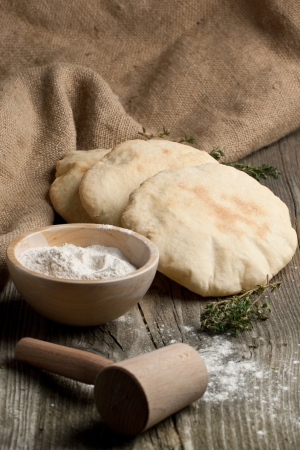 unleavened: Three fresh pitas bread, thyme and bowl of flour on old wooden table Stock Photo
