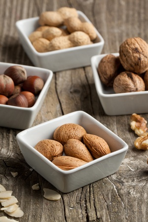 Assorted of whole and chopped nuts almond, hazelnut, walnut and peanut on old wooden table photo