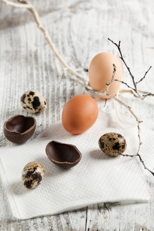 Assorted of quail, chicken and chocolate easter eggs on white wooden table photo
