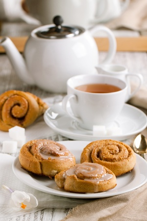 Breakfast with sweet cinnamon bun served on white wooden table photo