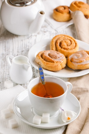 Breakfast with sweet cinnamon bun and cup of tea served on white wooden table photo