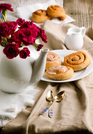 Breakfast with sweet cinnamon bun and carnation flower in teapot photo
