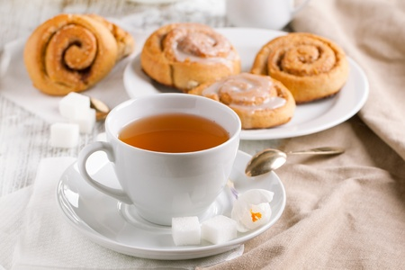 Breakfast with sweet cinnamon buns and cup of tea served on white wooden table photo