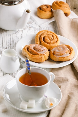 Breakfast with sweet cinnamon buns served on white wooden table  Focus on the buns photo