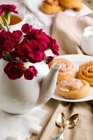 Breakfast with sweet cinnamon bun and carnation flower in teapot Stock Photo - 12934870