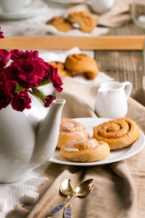 Breakfast with sweet cinnamon buns and carnation flower in teapot photo