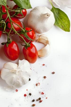 Ajos con racimo de tomates cherry, sal marina y pimienta sobre blanco Foto de archivo