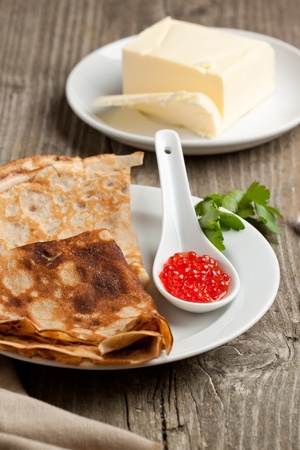 Plate of pancakes with red caviar and fresh butter on old wooden table photo