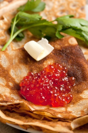 Red caviar with piece of butter and parsley on pancakes photo