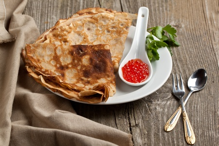 Plate of pancakes with red caviar and twig of parsley served with tableware on old wooden table photo