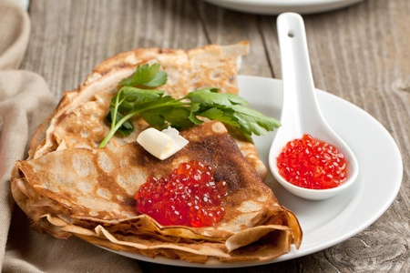 Plate of pancakes with red caviar, piece of butter and twig of parsley served on old wooden table photo