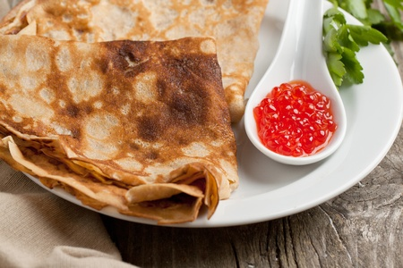 Colse-up of plate of pancakes with red caviar and twig of parsley served on white plate photo